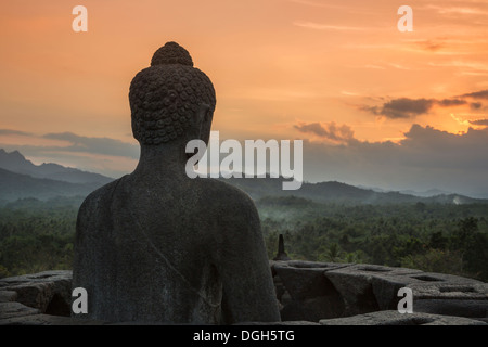 Buddha looking out over the surrounding countryside just after sunset at Borobudur, Central Java, Indonesia. - Stock Photo