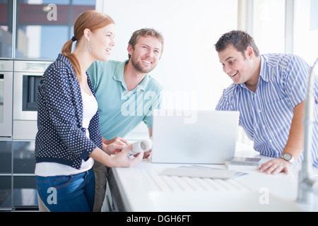 Young couple with salesman in kitchen showroom - Stock Photo