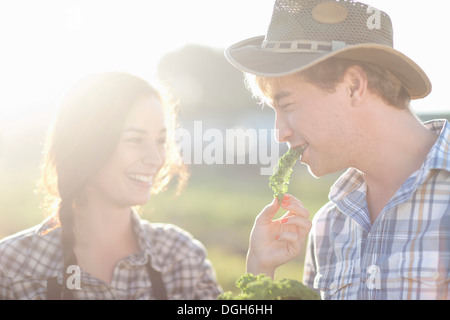 Young couple trying vegetables on farm - Stock Photo