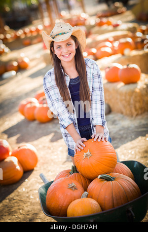 Preteen Girl Wearing Cowboy Hat Playing with a Wheelbarrow at the Pumpkin Patch in a Rustic Country Setting. - Stock Photo