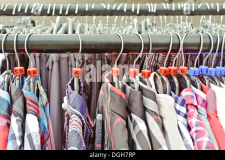 Selection of casual men's shirts XL and L size on a clothing rack - Stock Photo