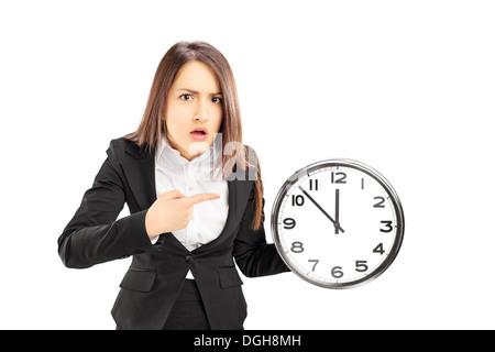 Angry young businesswoman pointing on a wall clock - Stock Photo