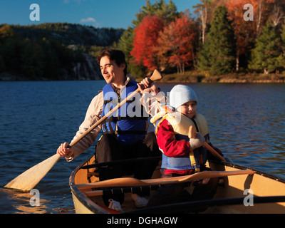 Father and his 3 year old son paddling a canoe. Fall nature scenic, Killarney Provincial Park, Ontario, Canada. - Stock Photo