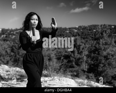 Dramatic black and white portrait of a young asian woman martial artis practicing nunchaku in the nature. Ontario, - Stock Photo