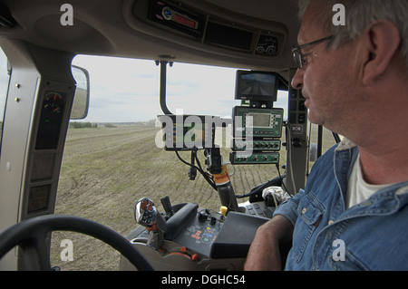 Case 225 tractor interior and farmer with GPS and Samson vacuum slurry tanker control panel injecting slurry into - Stock Photo