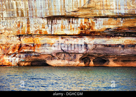 Naturally formed caves among the sandstone cliffs at Pictured Rocks National Lakeshore in Michigan's Upper Peninsula. - Stock Photo