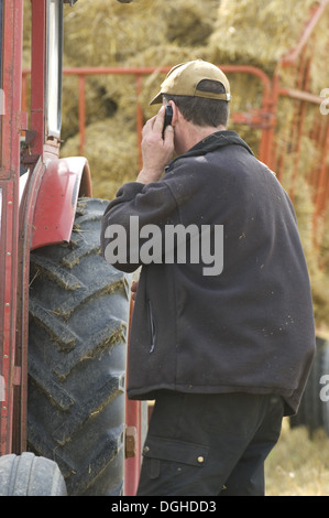 Farmer talking on mobile phone, standing beside tractor and trailer with straw bales, Sweden - Stock Photo