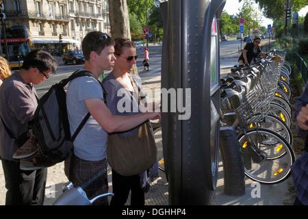 Paris France Europe French 7th arrondissement Quai Branly Velib bike share system station bicycle rental man woman - Stock Photo