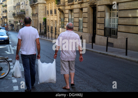 Paris France Europe French 9th arrondissement Rue Jean-Baptiste Pigalle man father son carrying groceries bag - Stock Photo