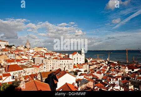 View from Miradouro Santa Luzia over the Alfama district on the Tagus river, on the right the church Igreja Sao - Stock Photo