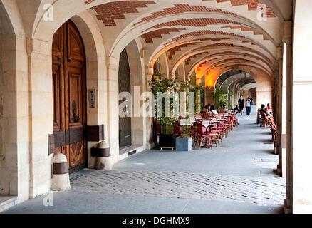 Arcade with a restaurant terrace on the Place des Vosges, Marais district, Paris, Ile de France region, France, - Stock Photo