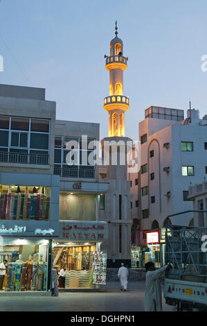 Street scene in old souq of Dubai with the minaret of a small mosque in the evening, Dubai, United Arab Emirates, - Stock Photo