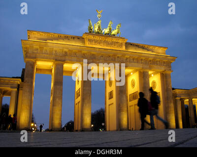 People walking in front of the Brandenburg Gate at dusk, Berlin - Stock Photo