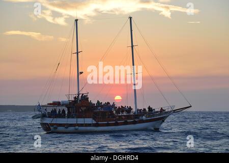 Sailing ship at sunset near Oía, Santorini, Cyclades, Greek Islands, Greece, Europe - Stock Photo