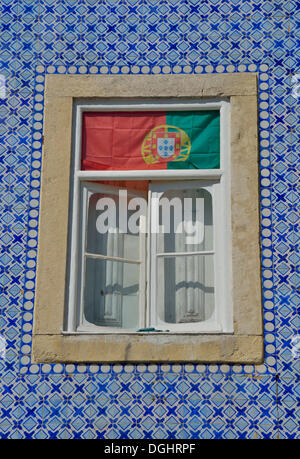 House facade with azulejos wall tiles and the Portuguese flag in the window, historic city district, Alfama, Lisbon - Stock Photo