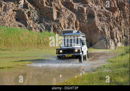 Safari vehicle in the Hoarusib river valley, Purros, Kaokoland, Kunene, Namibia - Stock Photo