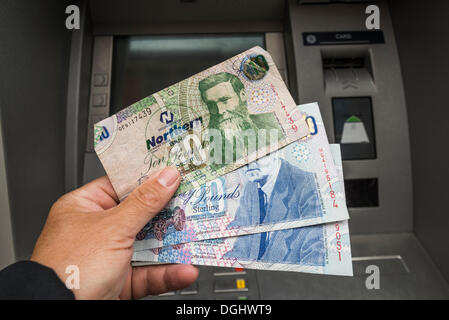 Northern Ireland 10 and 20 pound notes held in a hand in front of an ATM, Northern Ireland, United Kingdom - Stock Photo