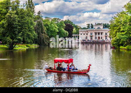 Tourists enjoy a gondola trip on the lake in Lazienki Park in Warsaw with the Palace in the background. - Stock Photo