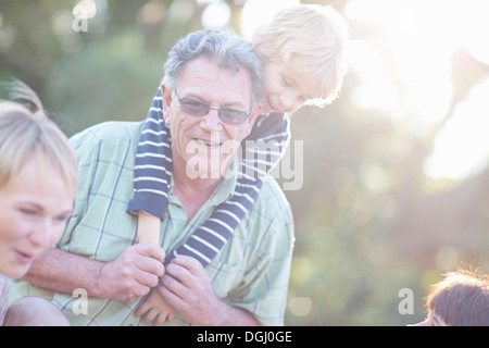 Grandfather giving grandson piggy back - Stock Photo