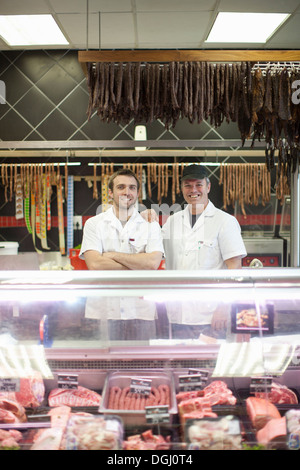 Portrait of two male butchers in shop - Stock Photo