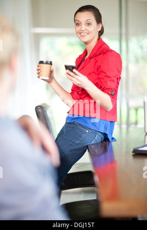 Young woman in office with cell phone and coffee - Stock Photo