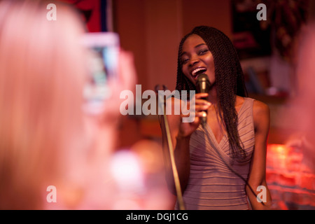 Young woman singing with microphone - Stock Photo