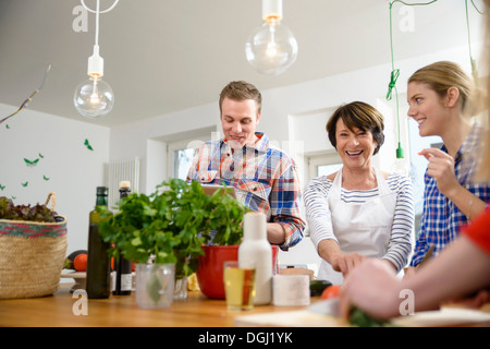 Mother with grown up children preparing food in kitchen - Stock Photo