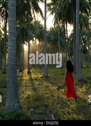Woman wearing red dress walking in forest of palm trees - Stock Photo
