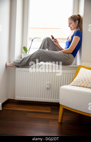 Young woman sitting on windowsill using cell phone - Stock Photo