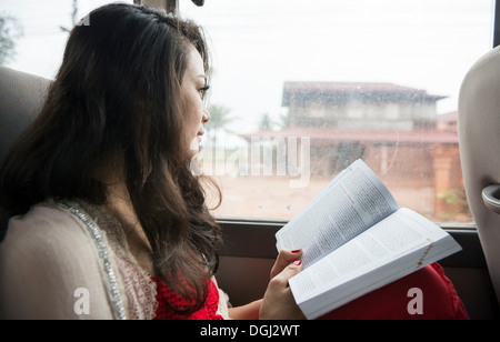 Woman looking out of window on bus with book - Stock Photo