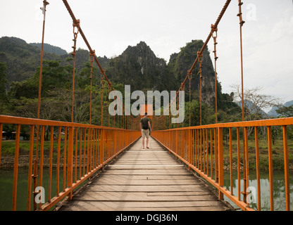 Man on bridge over river, Vang Vieng, Laos - Stock Photo
