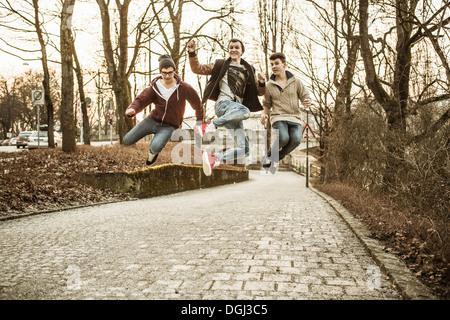 Three teenage boys jumping in park - Stock Photo