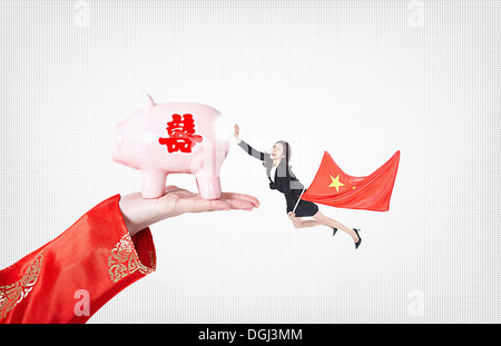 a business woman with a flag of chine holding a piggy bank - Stock Photo