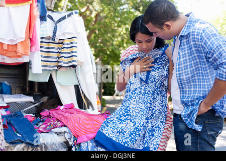 Young woman holding sundress with man watching - Stock Photo