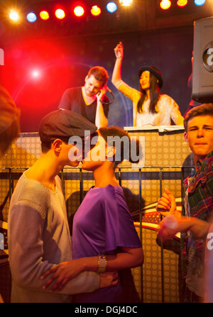 Young couple kissing at party, disc jockey in background - Stock Photo