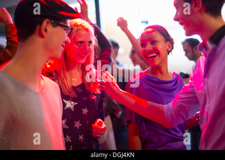 Four young adults laughing at party - Stock Photo