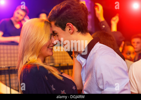 Young couple face to face at party, group behind - Stock Photo