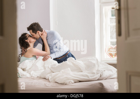 Mid adult couple kissing on bed - Stock Photo