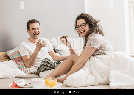 Mid adult couple having breakfast in bed - Stock Photo