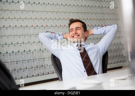 Businessman leaning back in chair with arms behind head - Stock Photo