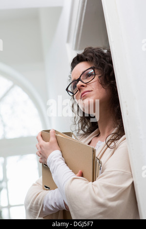 Woman leaning against wall holding folder - Stock Photo