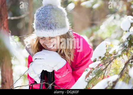 Young adult woman among snow-covered tree branches - Stock Photo