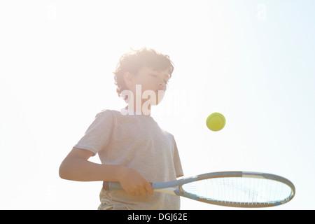Boy bouncing ball on tennis racket - Stock Photo