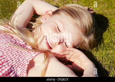 Child lying down on grass - Stock Photo