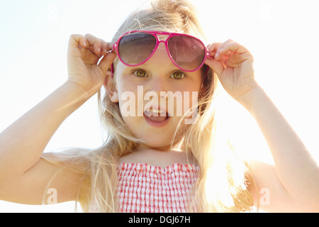 Child putting on sun glasses on hot sunny day - Stock Photo