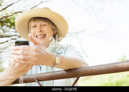 Senior woman smiling at message on mobile phone - Stock Photo