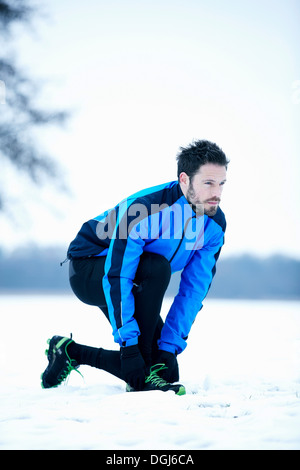 Man preparing for snow run - Stock Photo