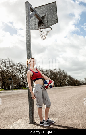 Woman with ball leaning against netball goalpost - Stock Photo