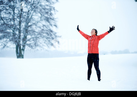 Woman in red tracksuit with outstretched arms - Stock Photo