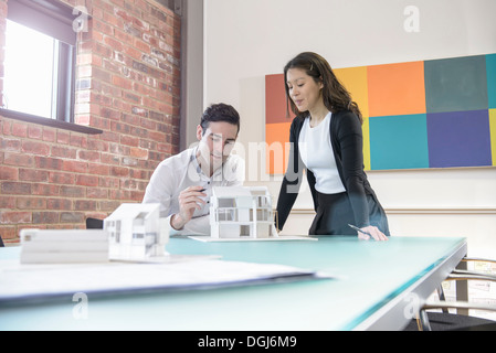 Architects working together on model of building in office - Stock Photo